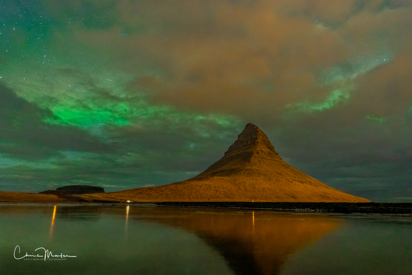 A stunning view of Kirkjufell mountain with the aurora borealis starting to show.
